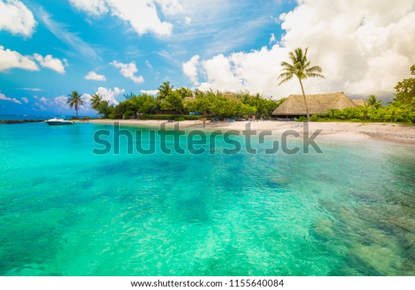 Huahine, French Polynesia. South Pacific. Tropical vacation landscape with lagoon, white sandy beach and palm trees on the island.