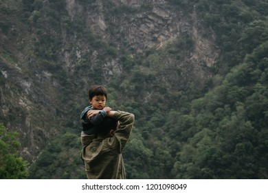 Hualien, Taiwan - April 7, 2018: Little son and his dad with mountain view at aroko National Park, Hualien, Taiwan