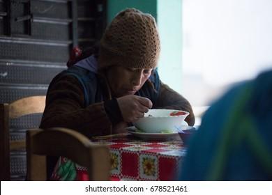 HUANCAYO, PERU - CIRCA 2017: An unidentified woman eat in a restaurant circa 2017, in Huancayo, Peru.