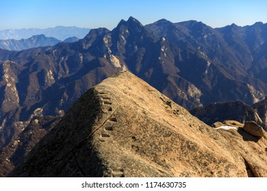 Huashan, Mount Hua - Huayin, near Xi'an in Shaanxi Province China. Dangerous Cliff Walk with Steep Vertical Drop-off, Famous yellow granite mountains of China. Steps chiseled into the mountainside