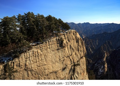 Huashan, Mount Hua - Huayin, near Xi'an in Shaanxi Province China. Cliff Scenery with Steep Vertical Drop-off, Famous yellow granite mountains of China. Layers of Mountains in the distance, exotic
