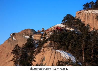 Huashan Sunrise, Mount Hua - Huayin, near Xi'an in Shaanxi Province China. Cliff Scenery with Steep Vertical Drop-off, Yellow granite mountains of China. Chinese Temple attached to mountain cliffs