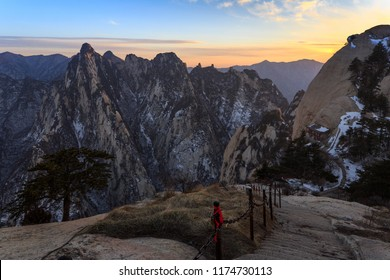 Huashan Sunset, Mount Hua - Huayin, near Xi'an in Shaanxi Province China. Cliff Scenery with Steep Vertical Drop-off, Yellow granite mountains of China. Chinese Temple attached to mountain cliffs