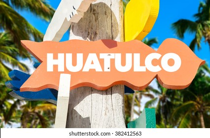 Huatulco welcome sign with palm trees