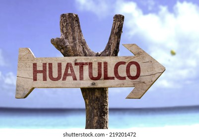 Huatulco wooden sign with a beach on background