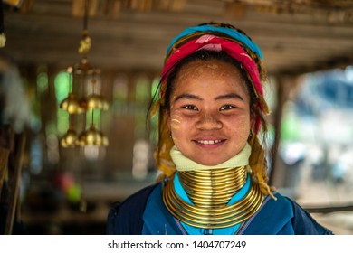 Huay Pu Keng, Thailand - March 22, 2019: Smiling long-neck Kayan Padaung woman in Huay Pu Keng village. Beautiful portrait of woman with neck rings brass coils.