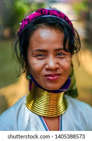 Huay Pu Keng, Thailand - March 22, 2019: Smiling long-neck Kayan Padaung woman in Huay Pu Keng village, Thailand. Beautiful portrait of woman with neck rings brass coils.