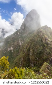 Huayna Picchu appear in front of our eye in between the fog while the clouds retreat. Steep walls with impressive valleys and mountains surround the old city of the Inca Empire, Peru, South America