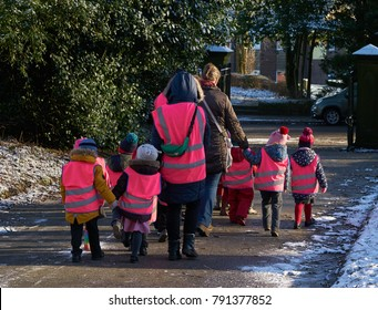 Huddersfield, UK - 12/11/2017: A group of small children, dressed for winter, with high visibility waistcoats, accompanied by adult guardians, walking. One adult carries a green first aid kit.