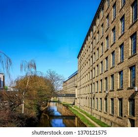 HUDDERSFIELD, UK - APRIL 11, 2019: View of the Huddersfield narrow canal running through the University of Huddersfield, Kirklees, West Yorkshire.