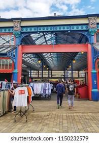 HUDDERSFIELD, UK - AUGUST 1, 2018: Unknown people walking around outside Huddersfield Indoor Market in the centre of Huddersfield, West Yorkshire, UK