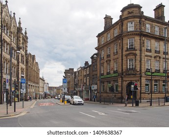 huddersfield, west yorkshire, United Kingdom - 20 May 2019: traffic and pedestrians on the road intersection of market street and westgate in the centre of huddersfield west yorkshire