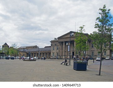 huddersfield, west yorkshire, United Kingdom - 20 May 2019: people and taxis in saint georges square huddersfield in front of the facade of the historic victorian train station