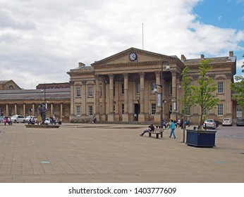 huddersfield, yest yorkshire, United Kingdom - 20 May 2019: people and taxis in saint georges square huddersfield in front of the facade of the historic victorian train station