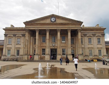 huddersfield, yest yorkshire, United Kingdom - 20 May 2019: people in saint georges square huddersfield in front of the facade of the historic victorian train station