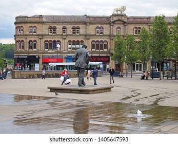 huddersfield, yest yorkshire, United Kingdom - 20 May 2019: People walking in st georges square in Huddersfield between the water fountains and surrounding buildings