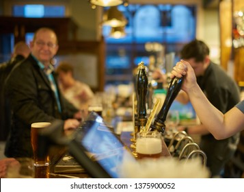 Huddersfield, Yorkshire, England - April 11 2019: Early Evening Inside an English Pub. Bartenders use hand pumps to pull pints of beer.