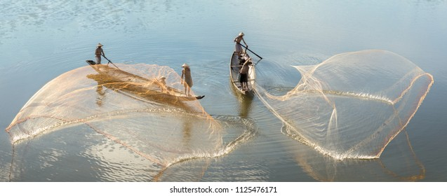 HUE CITY, VIETNAM - JUNE 18, 2018: Fishermen throw a fishing nets. Bridge survey. Morning view