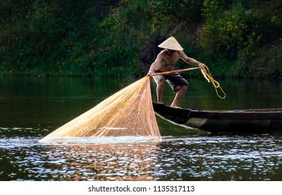 HUE CITY, VIETNAM - JUNE 18, 2018: Fishermen throw a fishing nets. Bridge survey. Morning view