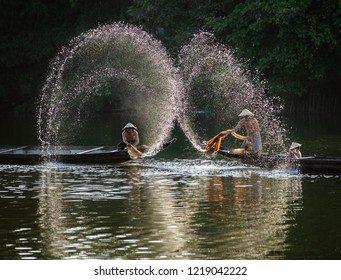 HUE CITY, VIETNAM - JUNE 18, 2018: Vietnamese fishermen clean up the nets before they start catching fish in the river. Morning view. Hue city, Vietnam