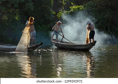 HUE CITY, VIETNAM - JUNE 18, 2018: Vietnamese fishermen throw a fishing nets for they start catching fish in the river. Morning view. Hue city, Vietnam