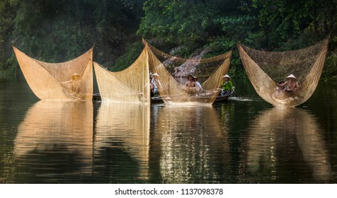 HUE CITY, VIETNAM - JUNE 19, 2018: Fishermen throw a fishing nets. Bridge survey. Morning view