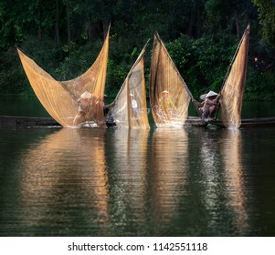 HUE CITY, VIETNAM - JUNE 19, 2018: Fishermen throw a fishing nets. Morning view. Hue city, Northern Vietnam