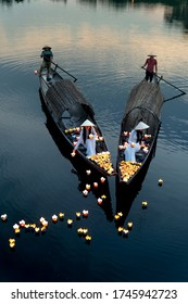 Hue City, Vietnam - May 8, 2020: Two Vietnamese girls with wihte tradition Ao Dai are lighting candle in lantern to pray in the river. Ao dai is famous traditional costume for the women in Vietnam.