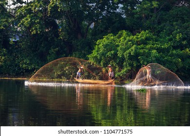 Hue city, Vietnam-April,11 2018: Vietnamese fishermen throw the big casting net into the river and then draw it back in Hue City, Vietnam