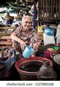 Hue, Vietnam - 03/23/2019: Vietnamese senior lady with plastic jug at Hue street market, Vietnam