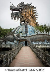 Hue, Vietnam - 03/24/2019: Huge and scary stone dragon with spikes and open mouth with teeth in profile view with footpath at abandoned water park, Thuy Tien lake, Hue, Vietnam