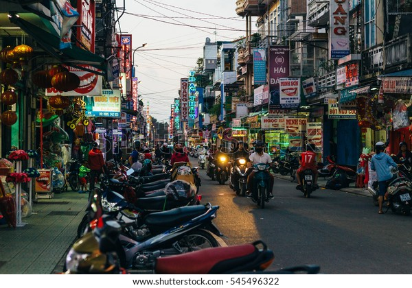 HUE, VIETNAM, 28 DECEMBER 2016 : Evening view of colorful Hue city street as people ride on the motorbikes passing by .
