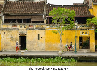 HUE,  VIETNAM - AUGUST 31, 2017:  Two vietnamese are walking / riding a  bicycle  along river in the old town in Hue.
