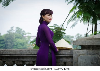 HUE,  VIETNAM - AUGUST 31, 2017:  Vietnamese is posing for a  photo in a traditional outfit,  riverside in Hue.
