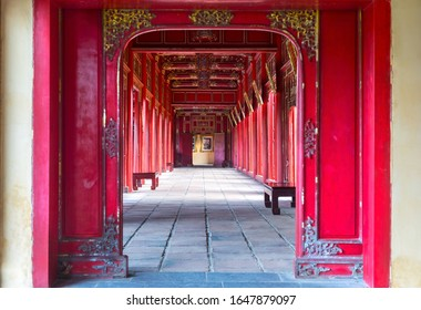 Hue, Vietnam - January 19, 2020: Symmetrical Corridor and Red Doors in the Forbidden Purple City, Historic Imperial Palace and United Nations World Heritage Site
