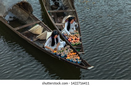 HUE, VIETNAM - JULY 18, 2018: Vietnamese girls set fire to ritual lanterns, which they send to sail on the river at night to urge luck. Bridge survey. Hue city