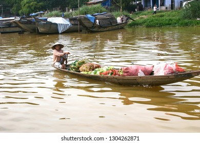 HUE, VIETNAM-NOV. 20, 2004:  A smiling woman uses a small boat as she rows across the Perfume River with local produce going to market.