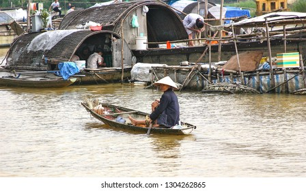 HUE, VIETNAM-NOV. 20, 2004:  A woman uses a small boat as she rows across the Perfume River with sampans, or houseboats, in the background.