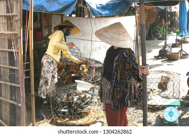 HUE, VIETNAM-NOV. 20, 2004: Women working with caged ducks and chickens at an outdoor market in the city.