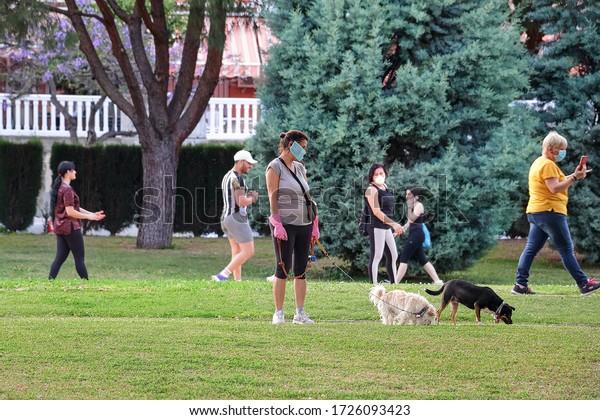Huelva, Spain - May 8, 2020: Woman walking her dog in a public park during Spanish lockdown due to Coronavirus