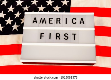 HUETTENBERG,GERMANY OCTOBER, 2018: Lightbox with letters - AMERICA FIRST Slogan - on an american national flag.