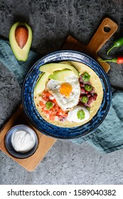 Huevos Rancheros Tostadas, Mexican breakfast consisting of toasted tortilla, chopped tomato and onion, jalapeno and bean mash, topped with fried egg, served with avocado slices and sour cream