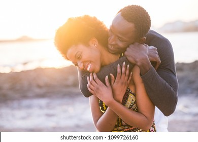 hug and enjoy black african race couple of model man and woman young 25 yearso old stay in love and touch joking and playing together. sunset in the background at the beach with waves and ocean.