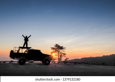 Hug the sky, view silhouette of a tourist standing on roof top of a 4WD. truck with colorful vivid sun light in the sky background, sunset at Huai Nam Dang National Park, Chiang Mai, Thailand.