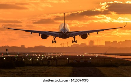 Huge airplane is landing at the airport during a nice colorful and cloudy sunrise. Amazing travel background with a passenger plane in the center.