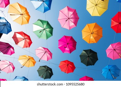 huge amount of colorful umbrellas hanging over a pedestrian street and forming a shadow