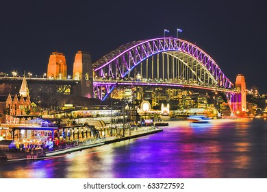 Huge arch of Sydney Harbour Bridge brightly illuminated during annual light show Sydney vivid sydney festival. Overseas passengers terminal and bridge reflect in blurred harbour waters.