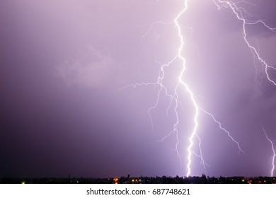 A huge and beautiful discharge of lightning in a stormy sky over a small town