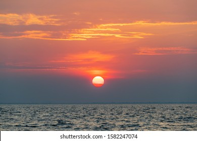 Huge or big sun set in the middle of the sea, isolated huge sun at twilight, magical moment at the sea, a giant orange sun set and golden sunshine reflected on sea.