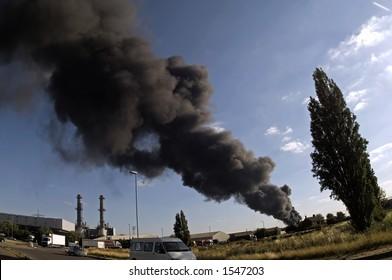 Huge black smoke plume from industrial fire, fisheye view, low angle.